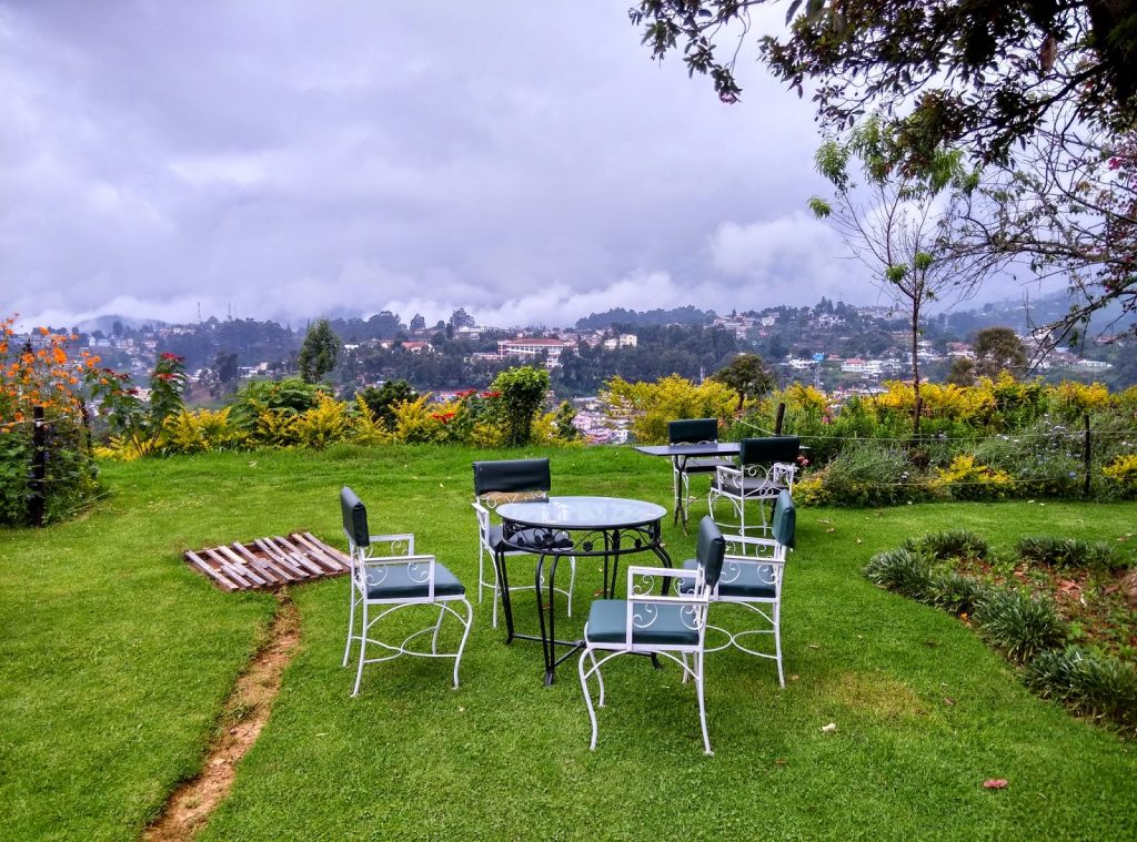 chair and table on a hill top stay and aerial view of coonoor