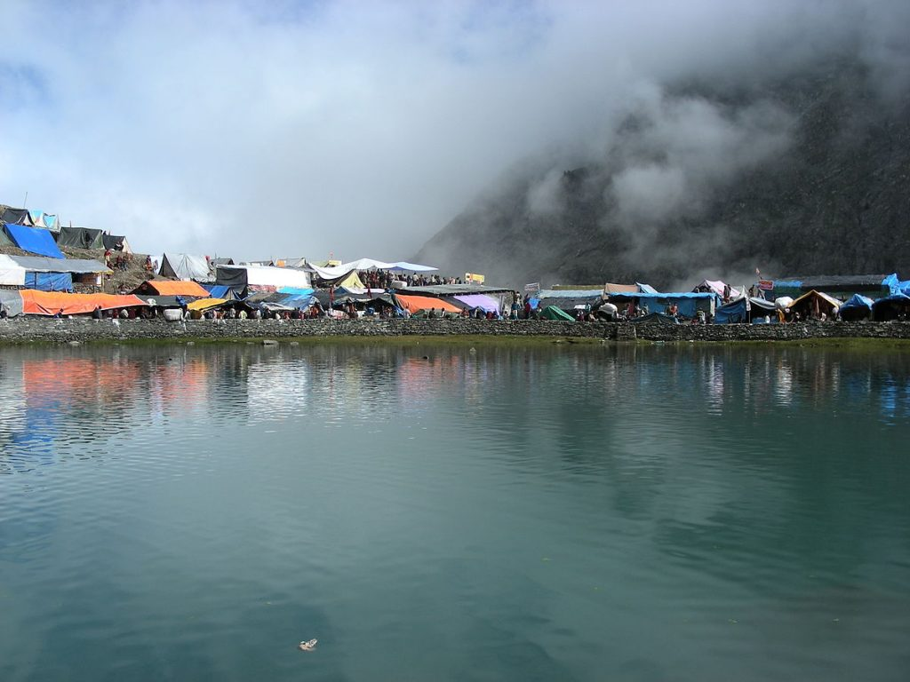 manimahesh lake with camps surrounding and clouds