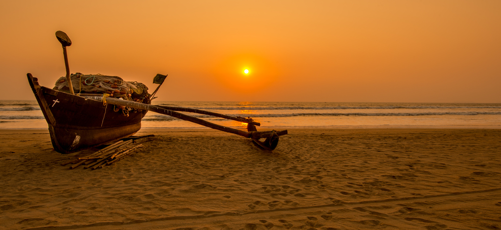 virgin beach with a boat during sunset in goa