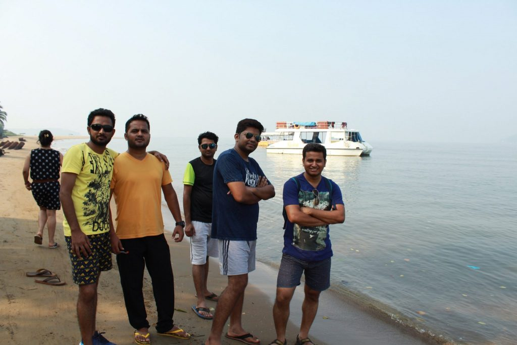 friends posing near beach and a vessel in background
