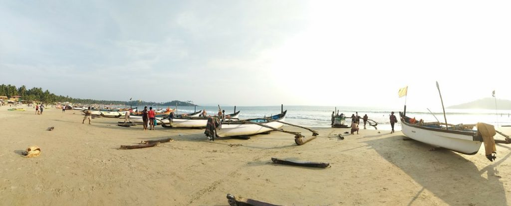 goa beach with boats and crowd moving