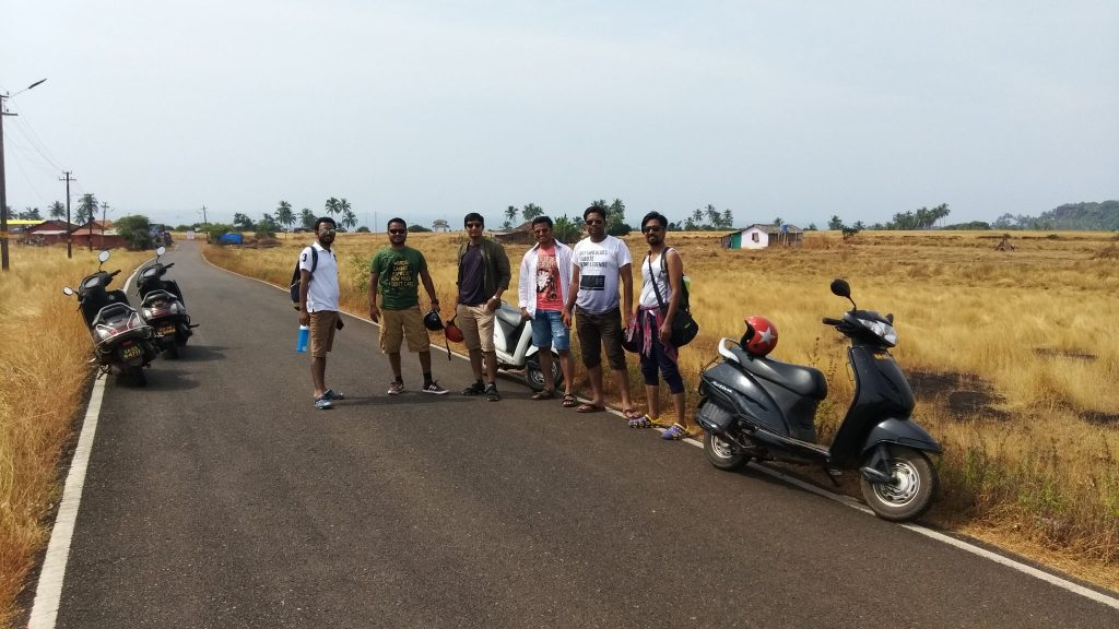 men posing roadside with scooty and yellow fields in background