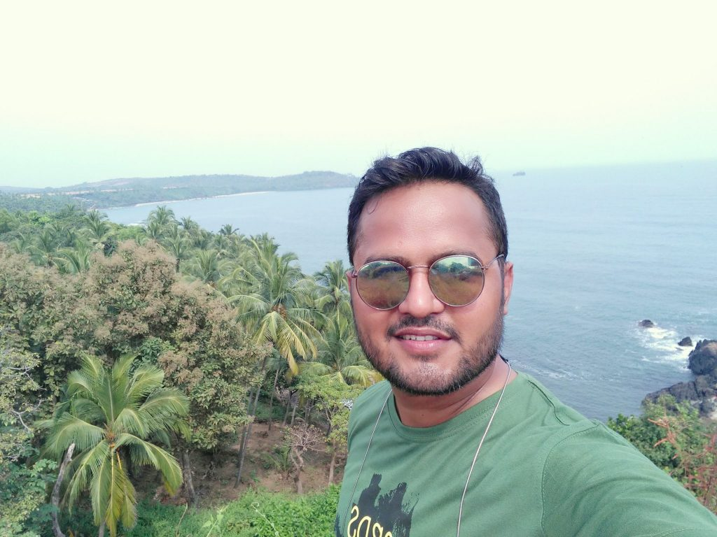 man taking selfie on hilltop with beach and coconut trees in background