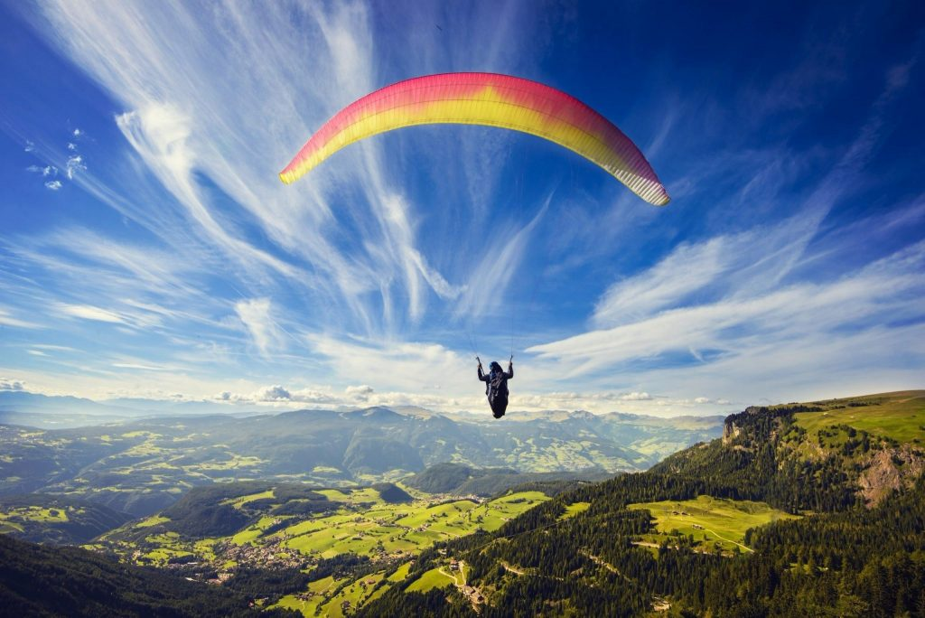 a girl doing paragliding mid of sky