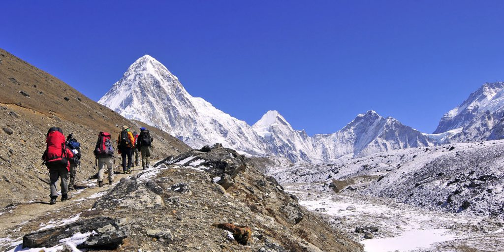 people trekking to himalayas in a group