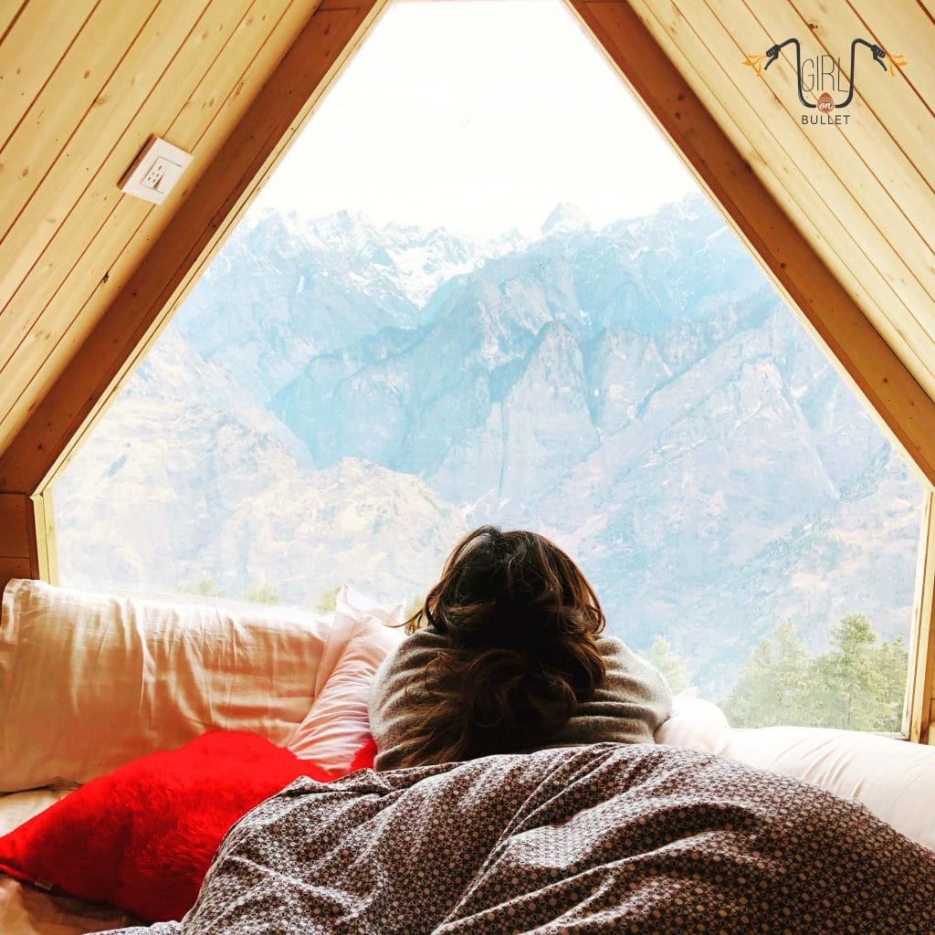 girl staring at mountain laying on bed