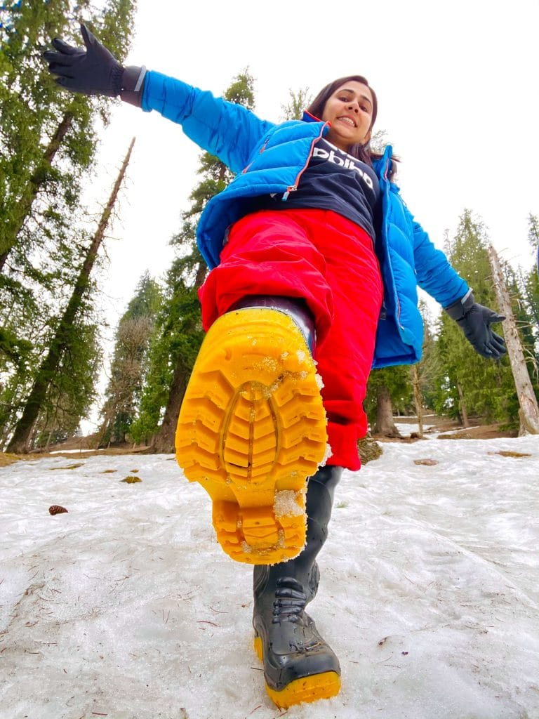 girl showing her yellow boots at snow